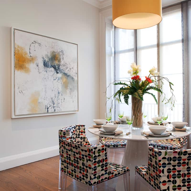 contemporary dining area with abstract artwork and colour pop contemporary chairs