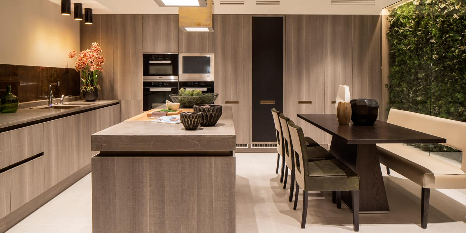 contemporary kitchen with timber kitchen island and faux green wall