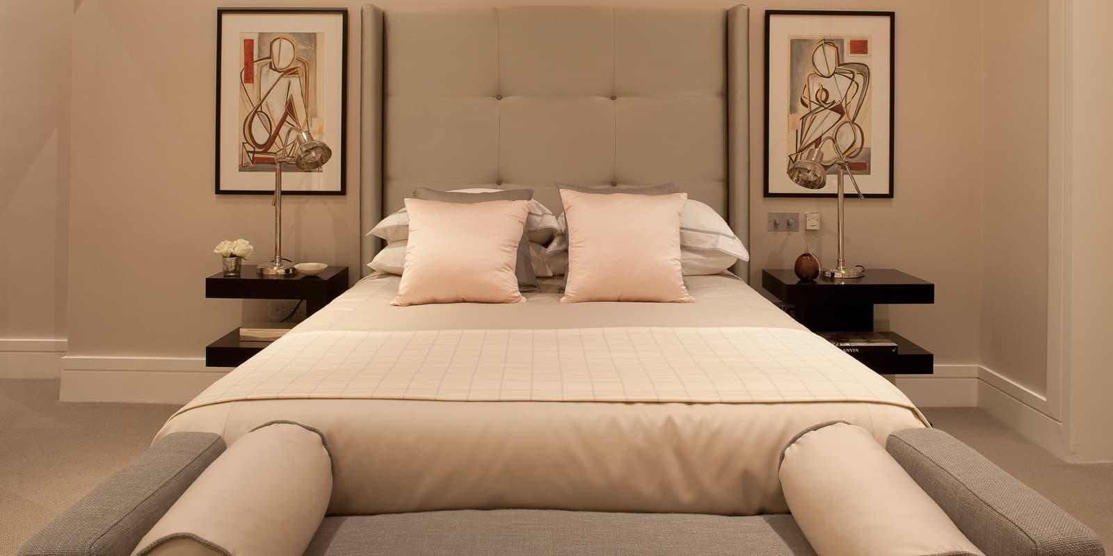 elegant bedroom of soft grey colour palette a grey chaise lounge at the foot of the bed