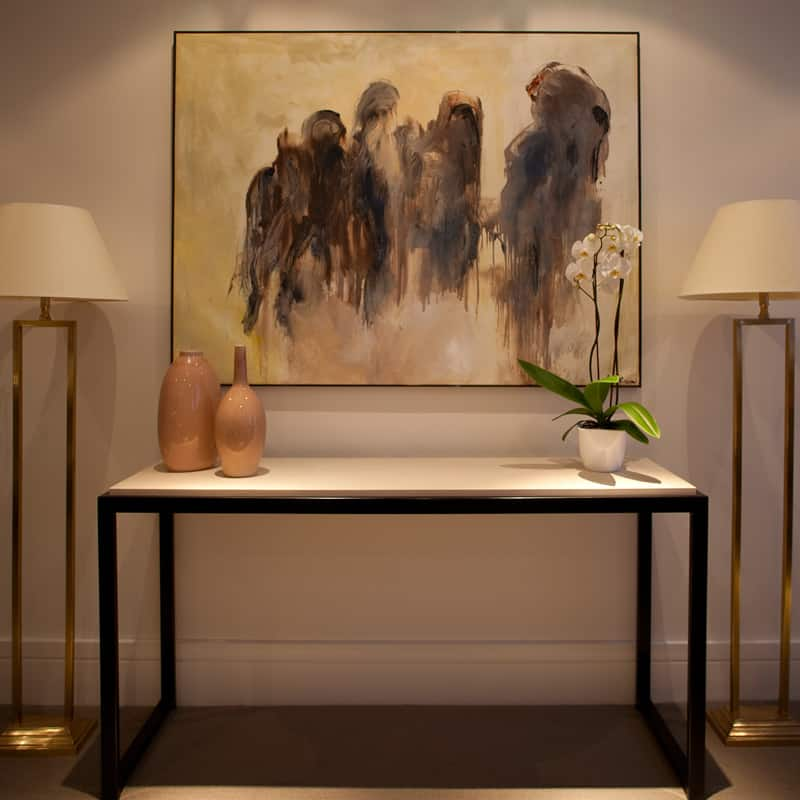 elegant console with floor lamps and contemporary artwork