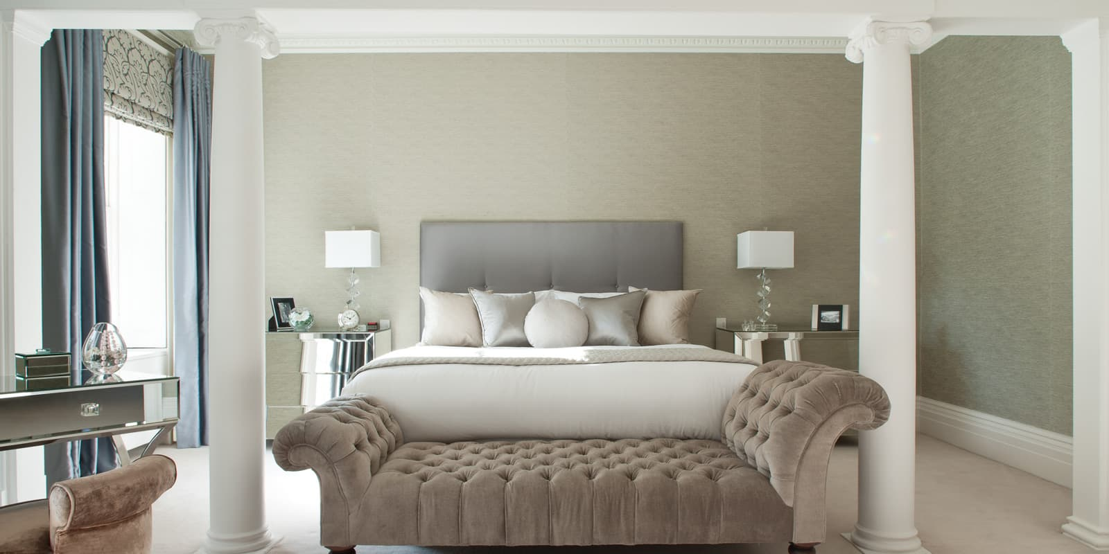 luxurious dream bedroom in green and grey colour palette with velvet chaise lounge positioned between white pillars