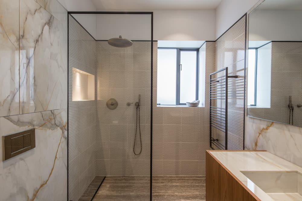 an industrial look bathroom with marble walls and black framed shower doors