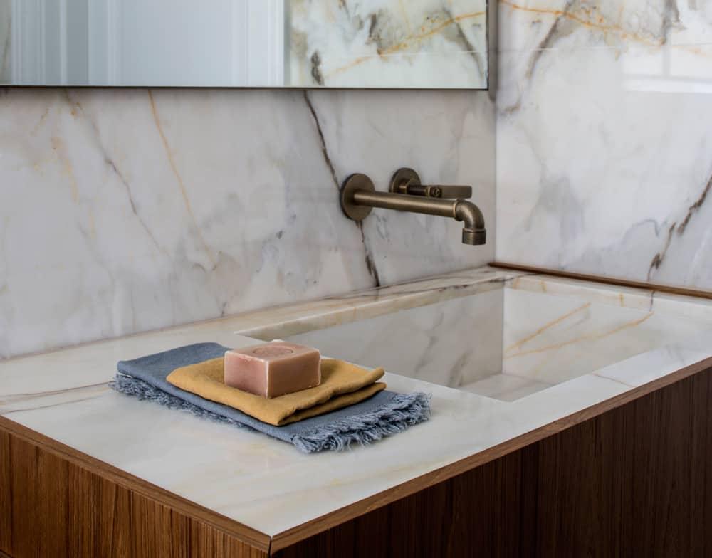 a marble bathroom vanity unit encased in teak in this industrial look bathroom