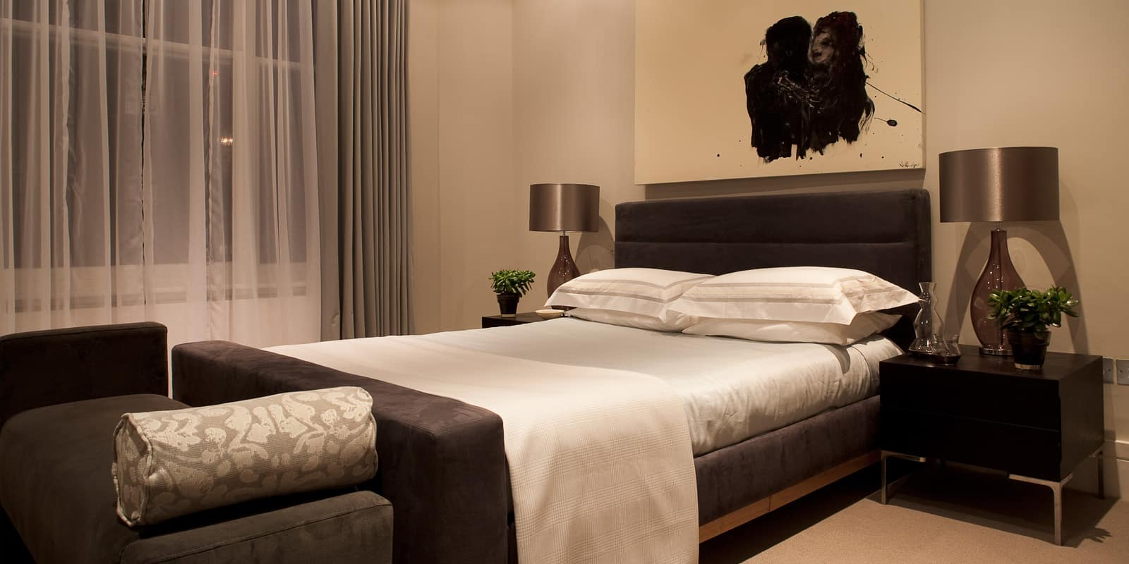 luxurious bedroom in a black and grey colour palette with hints of metallic textures