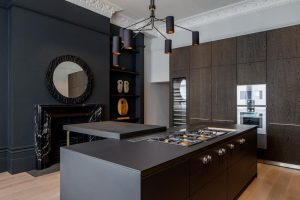 kitchen featuring dark brown kitchen island and dark grey wall with fireplace and round mirror