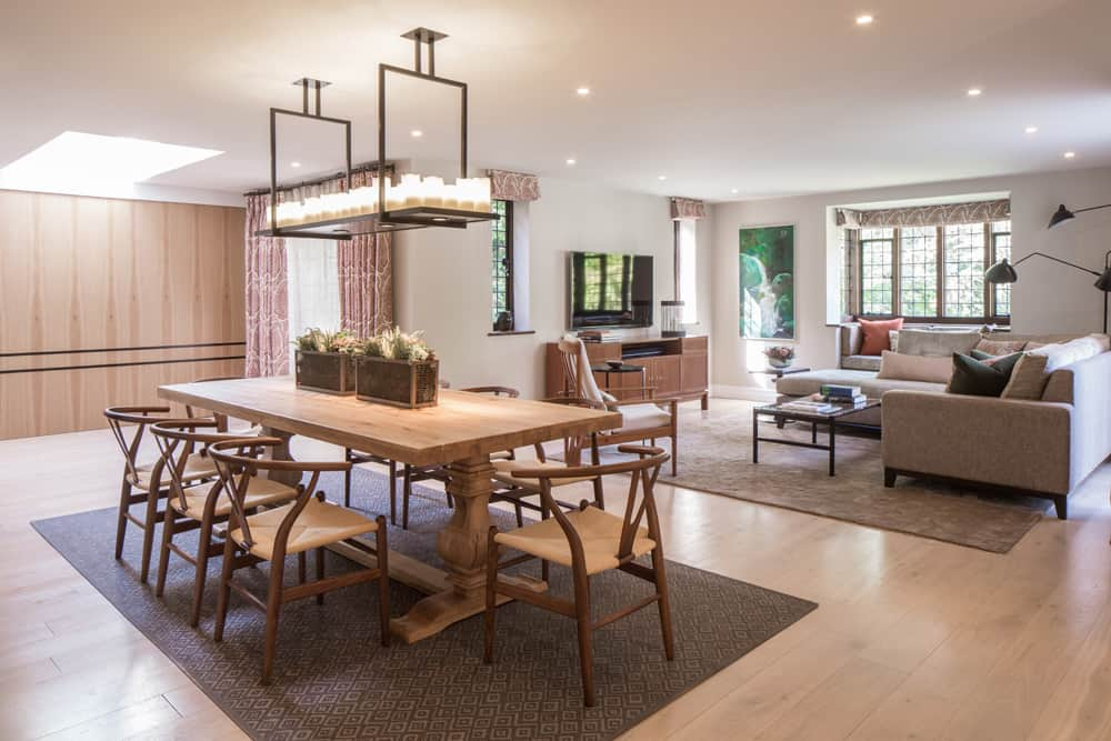 open plan dining area with 8-seater oak dining table and wishbone chairs and rectangular pendant light with candles