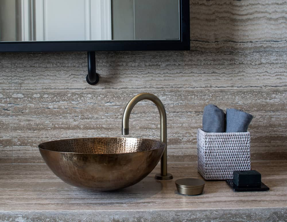 the sanitaryware in this contemporary bathroom is finished in vintage brass to complete the sophisticated industrial look