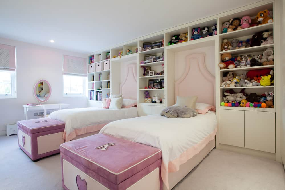 children's pink bedroom with single beds and shelving that extends to the ceiling