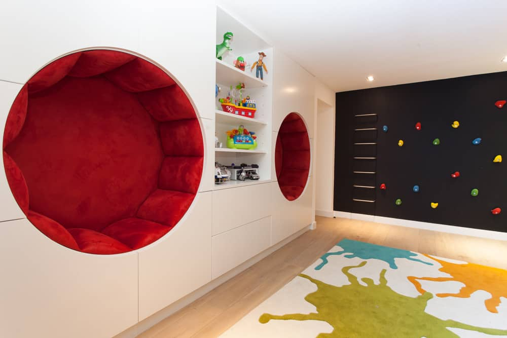 boys bedroom with red circular recessed seating and climbing wall built on a black chalkboard wall