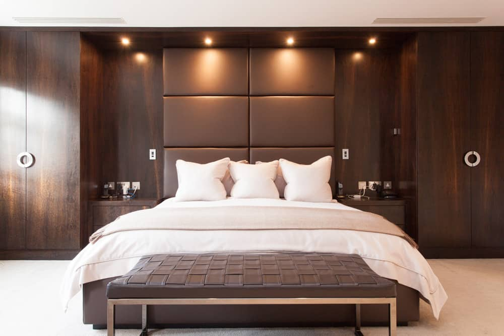 masculine master bedroom with brown leather headboard and contrasting cream carpet