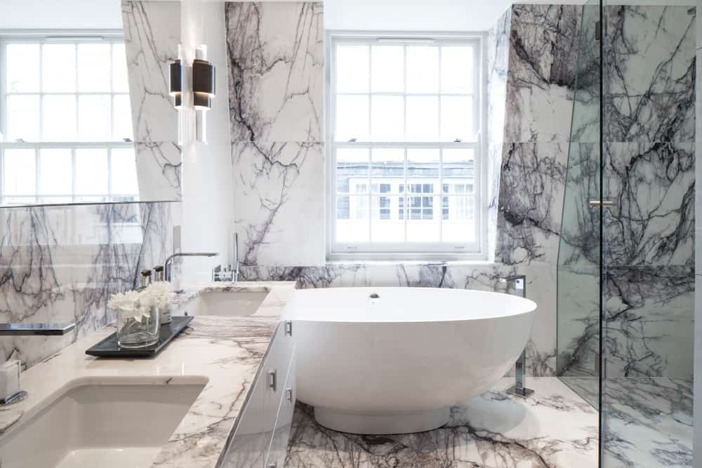 luxurious bathroom with veined marble and large white oval bath