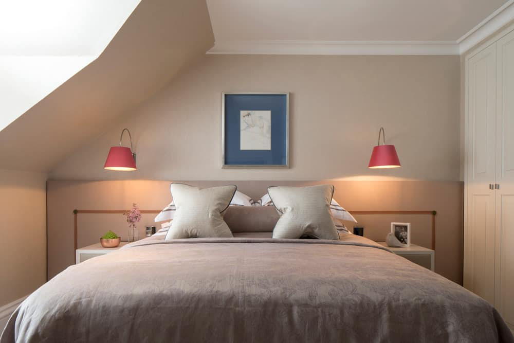 luxurious bedroom with pink wall lights and a full width headboard