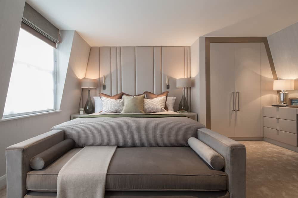 luxurious bedroom in neutral shades with leather headboard and grey chaise lounge at the foot of the bed
