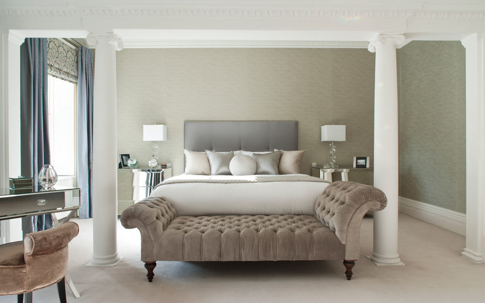 luxurious bedroom with white pillars in the centre of the room, shades of grey and green and a velvet chaise lounge at the foot of the bed
