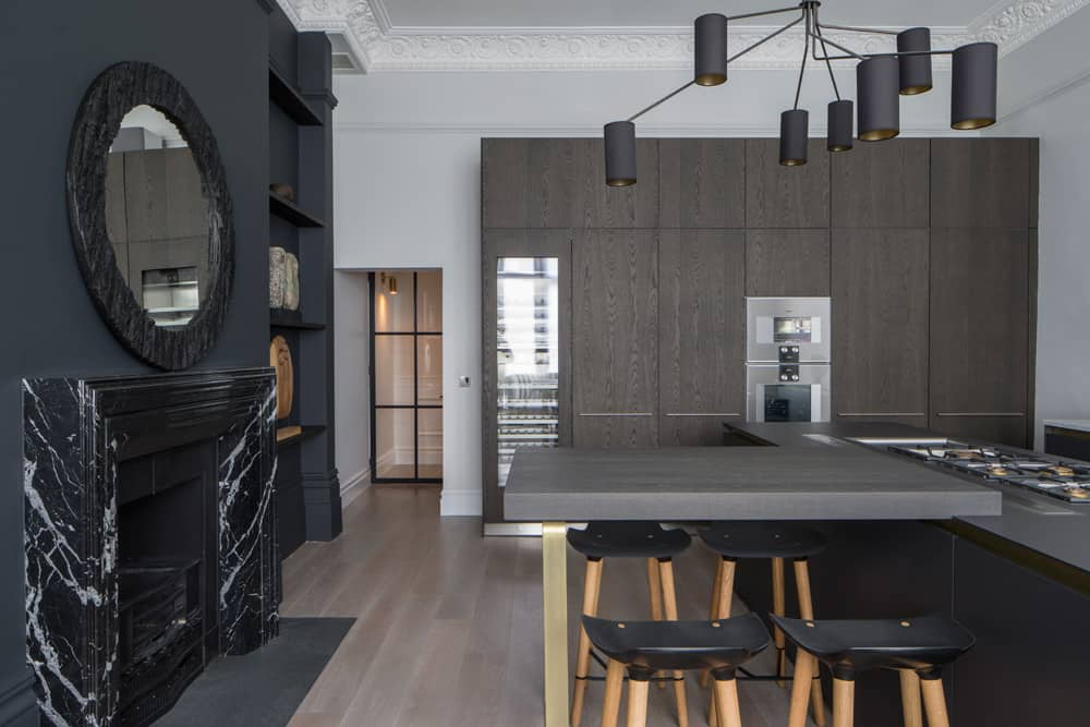 modern industrial kitchen with brown timber kitchen island and marble fireplace