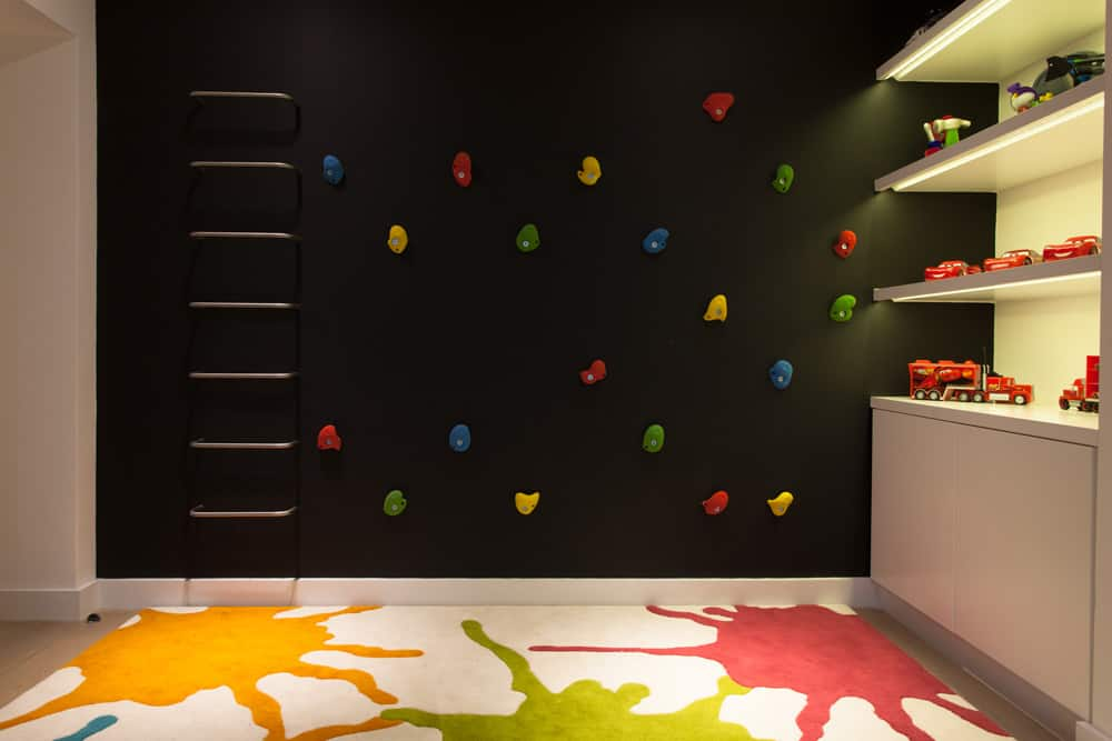climbing wall built onto black chalkboard paint with a bright rug and recessed shelving in this children's bedroom