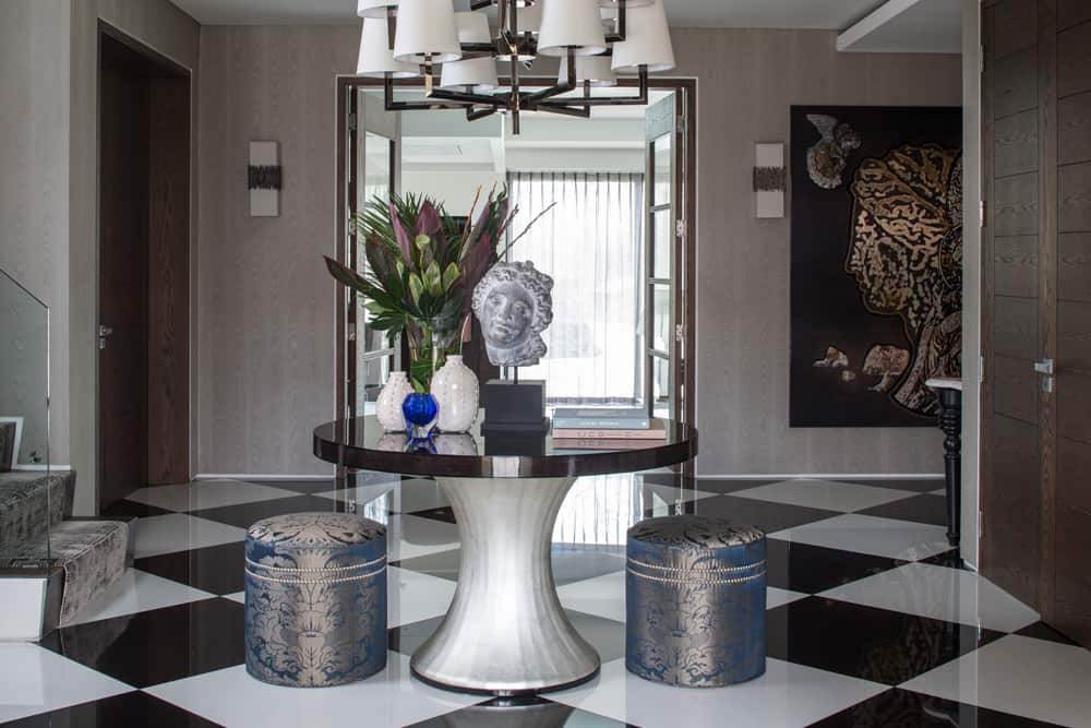 a grand entrance hall with oval table, silk footstools and black and white floor tiles