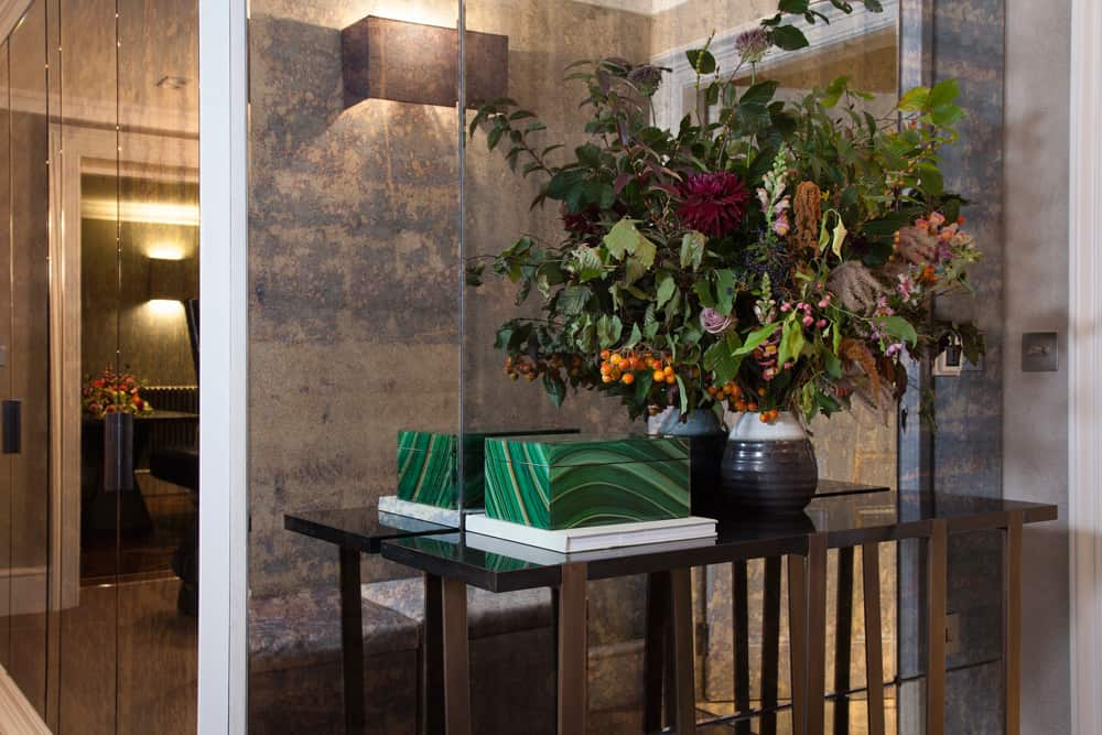 entrance hall with autumnal bouquet of flowers with emerald accessories and antiqued glass