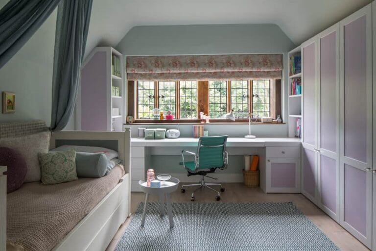 Girls pink bedroom design with white desk and pink wardrobes
