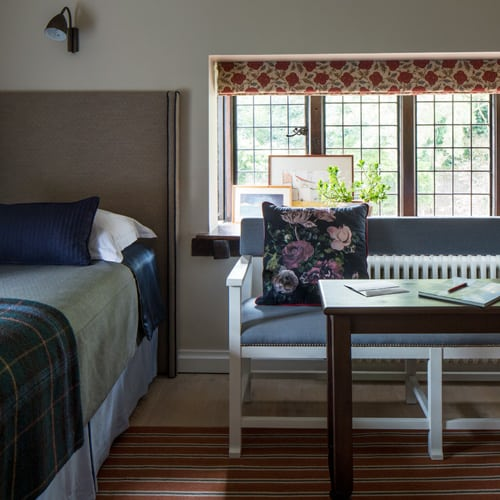 floral design roman blind and cushion in this guest bedroom by roselind wilson design