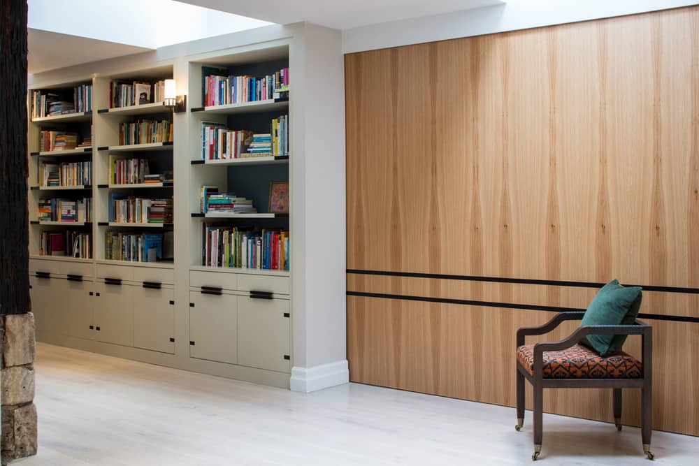 bespoke library joinery and a timber pocket sliding door that closes off the desk area by roselind wilson design