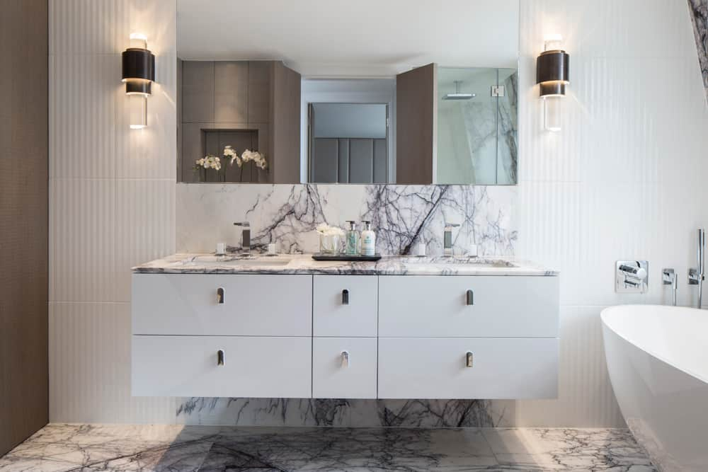 hotel luxury white floating bathroom vanity with Turkish lilac marble top and flooring and round freestanding bath by roselind wilson design