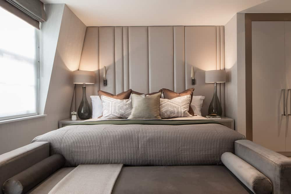 luxury bedroom in a neutral colour palette with ful-height leather headboard and chaise lounge at the foot of the bed by roselind wilson design