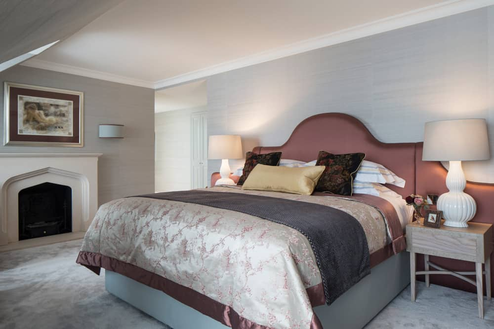 luxury bedroom with curved headboard and layers of textured bed throws and cushions by roselind wilson design