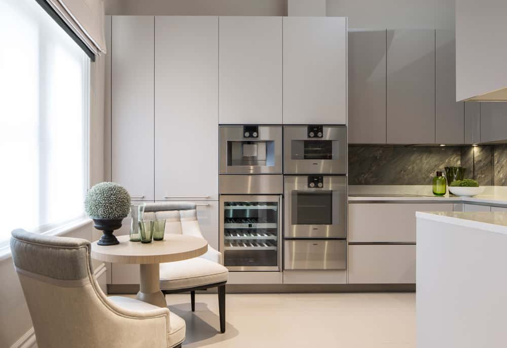 A bright contemporary kitchen with neutral colour palette, white cabinetry and window seat with small round light veneer table and two dining chairs.