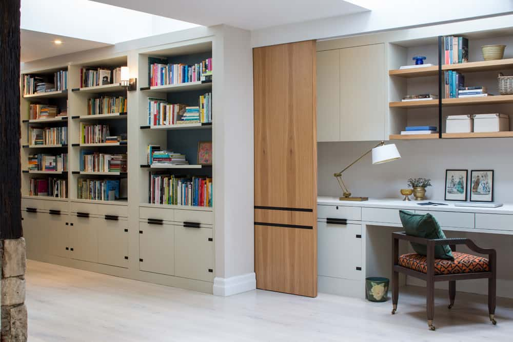 Home office work space that can be hidden from view by a timber sliding door that pockets to behind library shelving