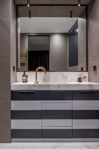 A black and white striped bathroom vanity paired with a Calacatta Oro marble countertop and striking metal framer mirror.