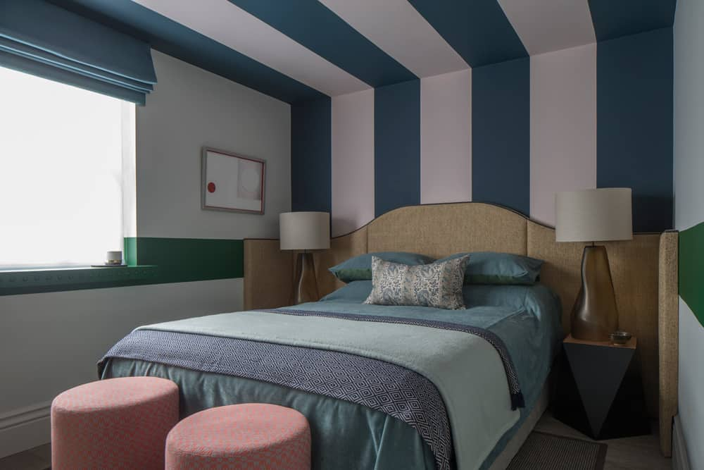 Blue stripes run up and over the ceiling of this bedroom with a textured headboard that extends cross the full width of the room.