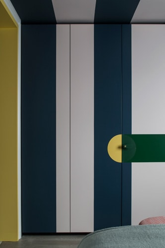 Blue and white vertical stripes on the built-in wardrobe doors contrast with the bright yellow and green of the joinery handle.