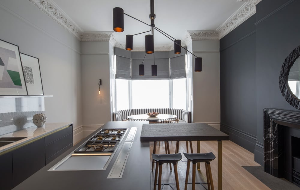 Black and white striped banquette seating in the bay window draws the eye right to the end of this contemporary monochrome kitchen with marble surround fireplace and striking pendant light fixture.