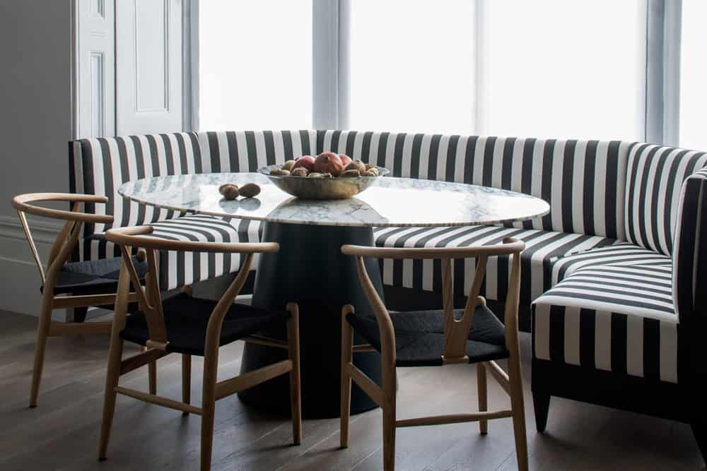 Black and white striped banquette seating in bay window with oval marble table and wishbone chairs by Roselind Wilson Design.