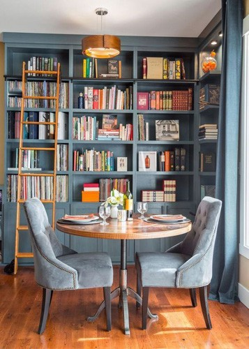 A breakfast area for two in a home library with grey blue colour palette and velvet upholstered dining chairs.