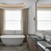 an elegant master bathroom with freestanding bath, large sash window, floor to ceiling curtains and coffered ceiling with LED lighting