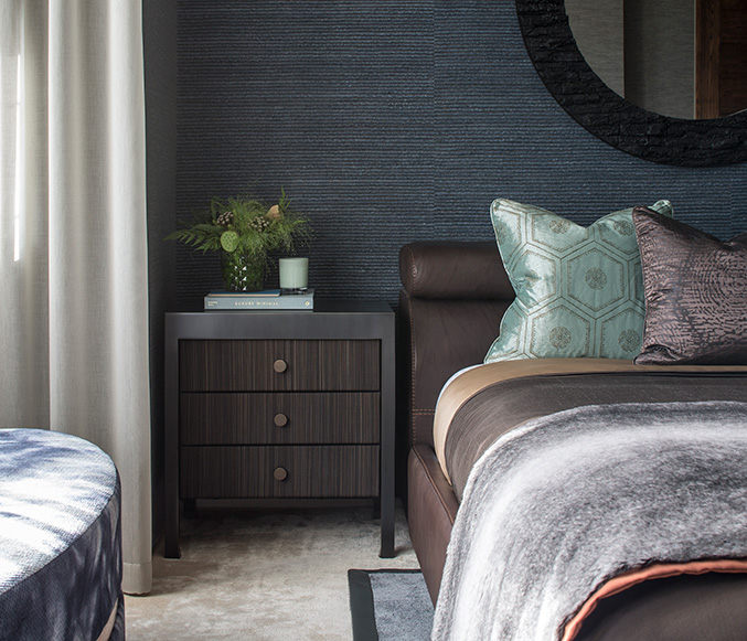 cosy bedroom with textured blue wallpaper and bespoke bedside table
