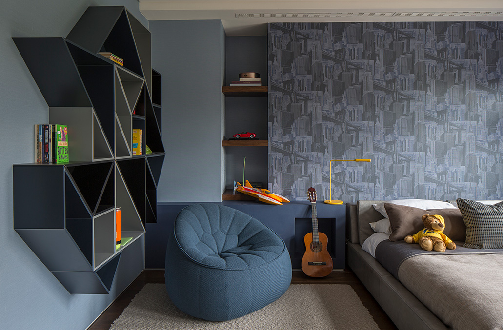 blue boys bedroom with patterned wallpaper and geometric shelving
