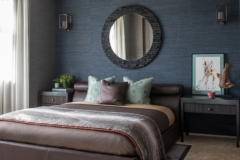 cosy bedroom with textured blue wallpaper and circular mirror