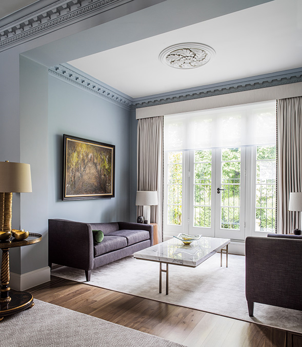 elegant reception room with blue walls and marble coffee table
