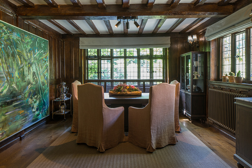 cosy mock-Tudor dining room with rustic chair covers and exposed beams