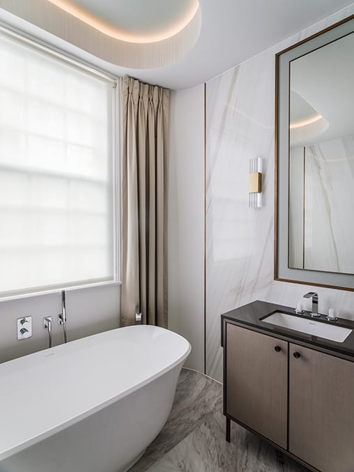bathroom with large freestanding bath and floor to ceiling curtains on either side of a sash window
