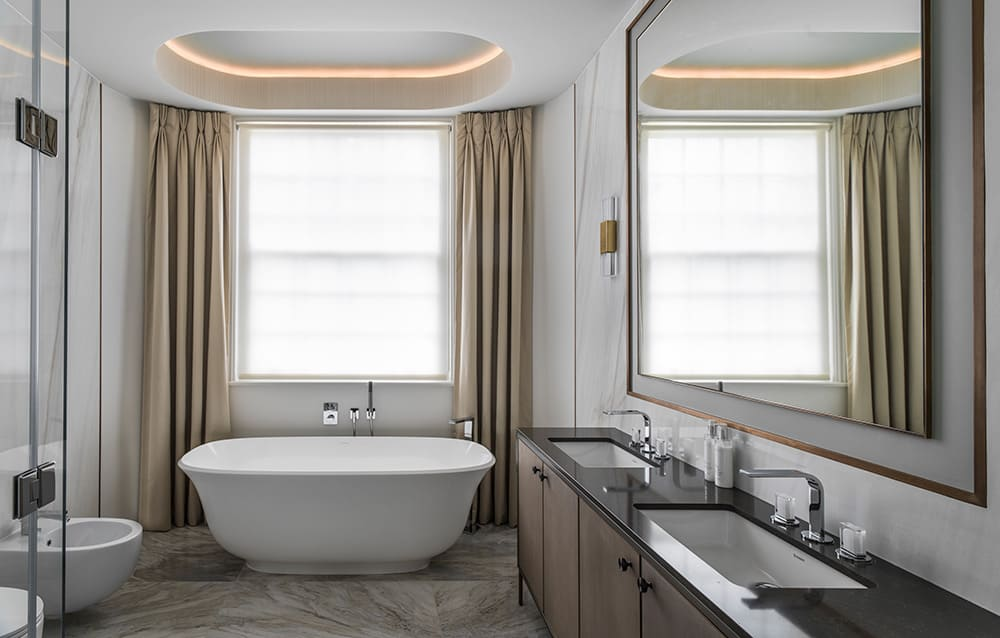 elegant master bathroom with large freestanding bath, sash window with floor to ceiling curtains and coffered ceiling with LED lights