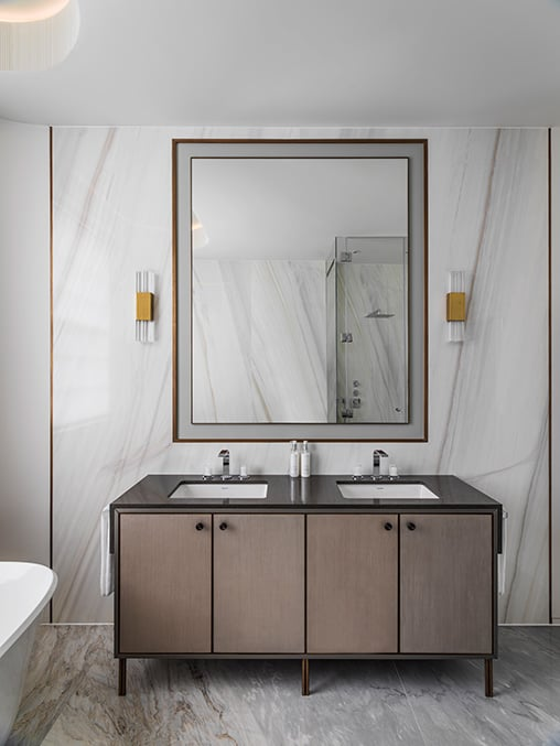 elegant bathroom vanity with brass wall lights on either side of a large bathroom mirror with bronze mirror surround