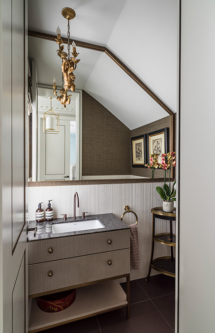 small cloakroom with textured surfaces, basin and bespoke chandelier