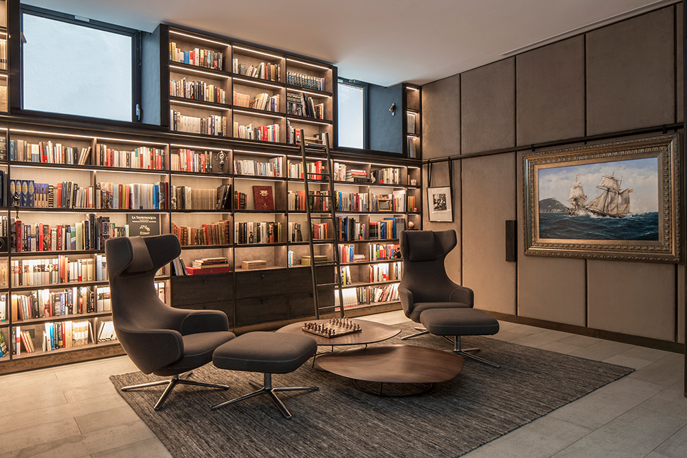 home library with floor-to-ceiling shelving and reclining chairs