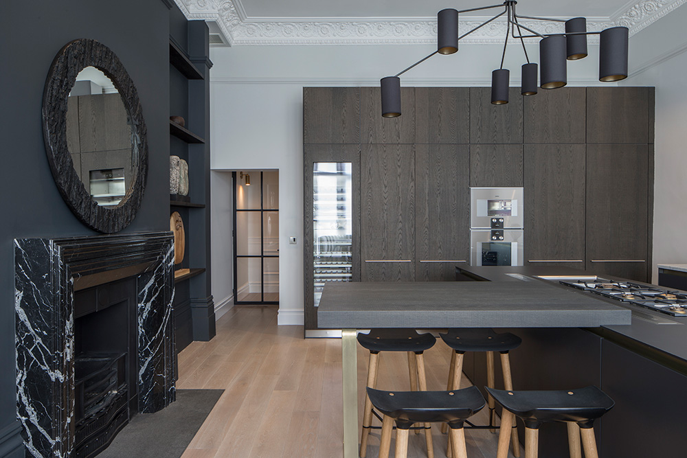 contemporary kitchen with dark grey wall and marble fireplace