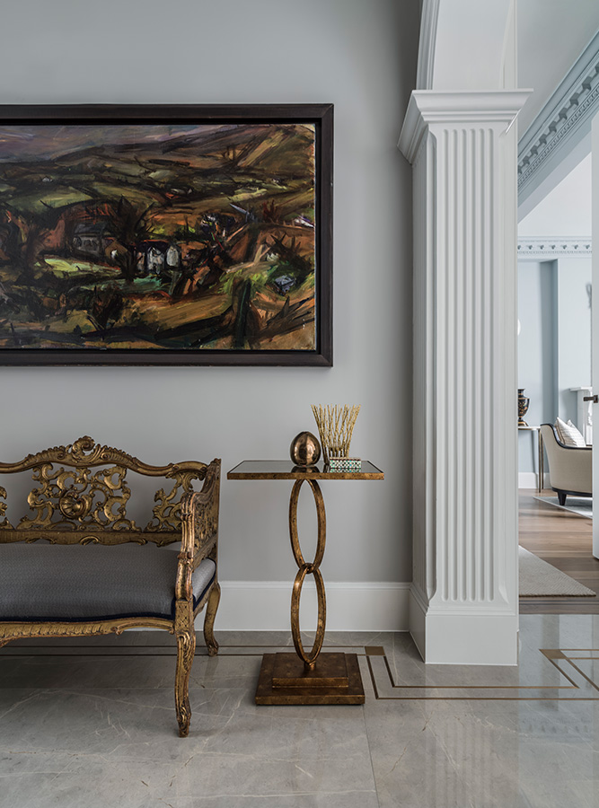 entrance hallway with decorative bench and gold leaf side table