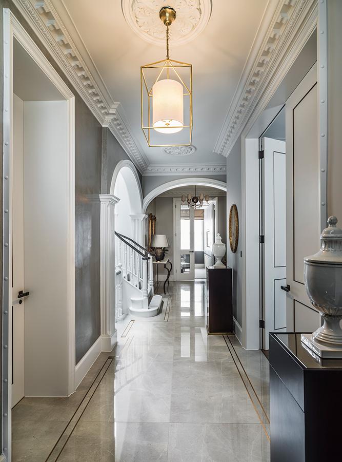 luxury entrance hallway flooring with bronze tramlines and pendant chandelier